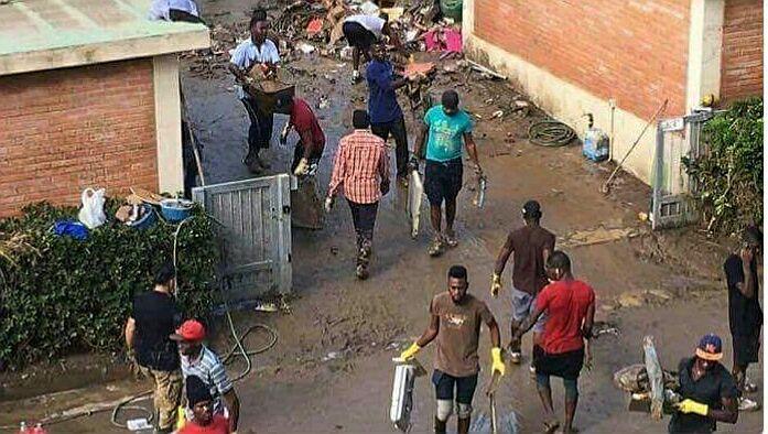 Una foto che invita a riflettere: un gruppo di migranti aiuta i Livornesi a ripulire le case da fango e detriti