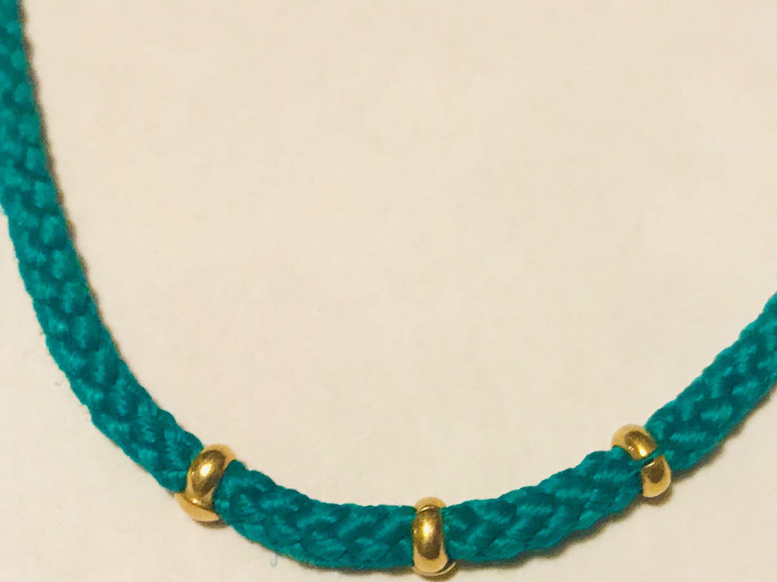 Il bracciale amuleto con il cordoncino verde e inserti in oro