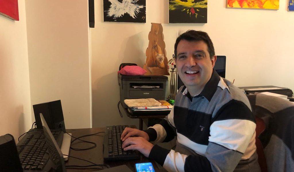 Andrea Ferrero, non vedente, circondato da tastiere dispositivi elettronici. Alle sua spalle alcuni dei suoi quadri.